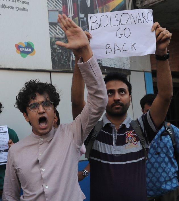 Ativistas gritam slogans enquanto seguram cartazes durante um protesto contra a visita do presidente...