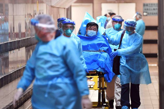 Medical staff transfer a patient suspected of having the new coronavirus in Hong Kong on Jan. 22,