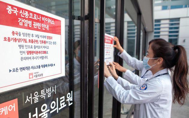 서울의료원 의료진이 감염 예방 강화를 위해 의료원 내외부에 관련 안내문을 부착하고 있는