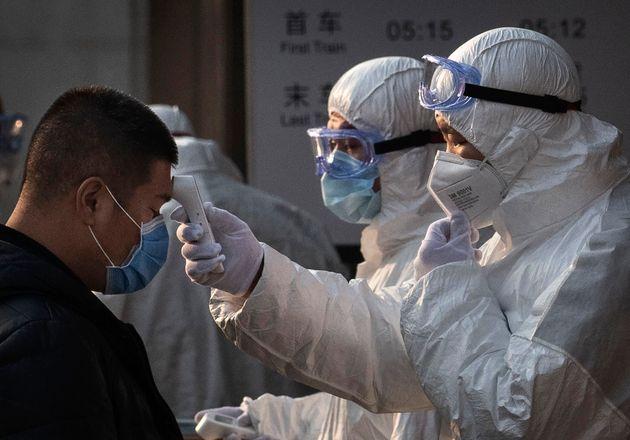 춘절인 25일 중국 베이징 지하철역에서보건당국에서 나온 직원들이 한 시민의 체온을 재고