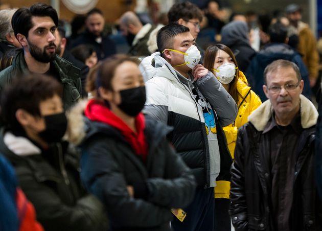 Les gens portent des masques par précaution en raison de l'éclosion de coronavirus en attendant à l'aéroport...