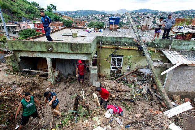 Moradores trabalham para limpar a lama e os detritos em torno das casas destruídas por um deslizamento...