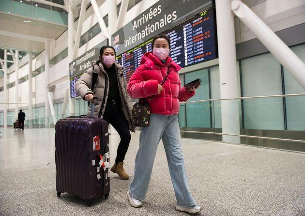人々は、国際到着時にコロナウイルスの大流行のために予防措置としてマスクを着用しています...