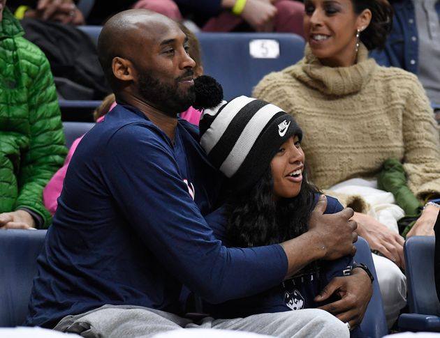 Kobe Bryant and his daughter Gianna watch the first half of an NCAA college basketball game between Connecticut...