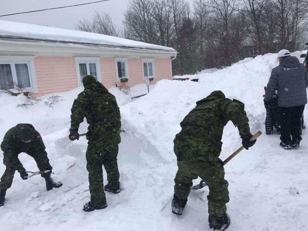 Members of the Armed Forces help clear snow in