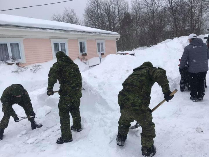 Members of the Armed Forces help clear snow in Newfoundland.