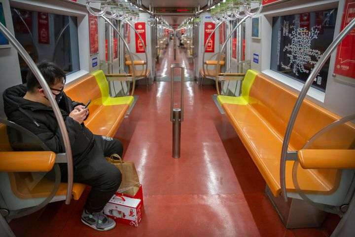 A man wearing a face mask rides a nearly empty subway train in Beijing on Jan. 26, 2020.