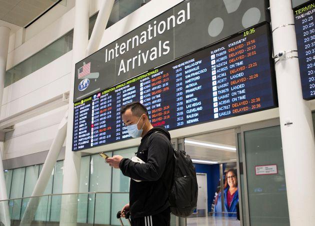 Un homme porte un masque à l'aéroport Pearson de