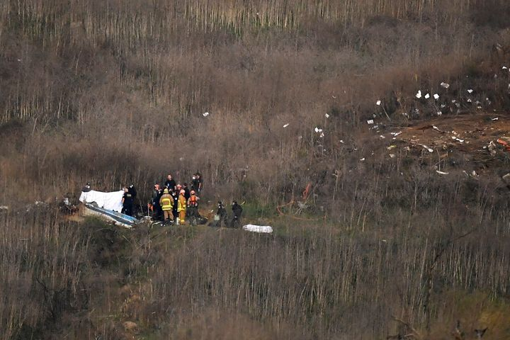 A body is covered, left, while another sits at right at the scene of a helicopter crash that killed former NBA basketball pla