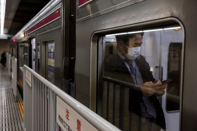 A commuter wearing a mask waits for a train to depart at Shinjuku Station in Tokyo, Monday, Jan. 27,...