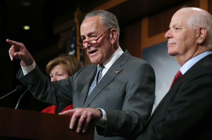 Senate Minority Leader Chuck Schumer speaks as Sen. Ben Cardin (right) and Sen. Tammy Baldwin (left) look on at a news confer