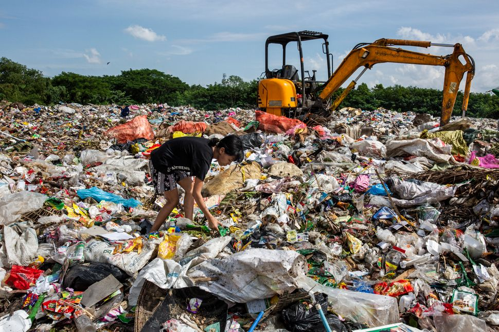 Aye Lay, 19, searches for plastic bottles to sell to the recycle shop at the Dala dump site, Yangon division,...