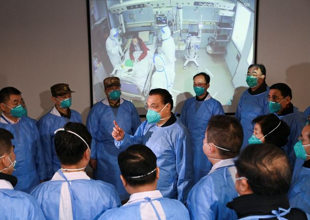 Chinese Premier Li Keqiang, wearing a mask and protective suit, speaks to medical workers on Jan. 27...