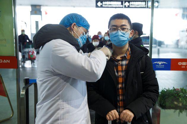 中国の空港で、医療当局者から体温を計られている男性=2020年1月27日