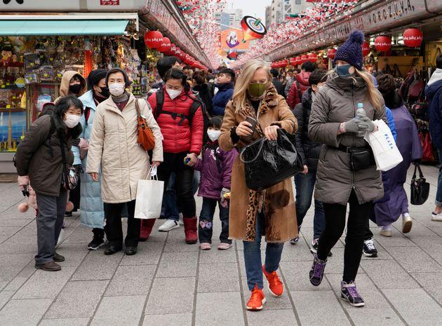 東京・浅草寺をマスク姿で歩く観光客ら=2020年1月27日