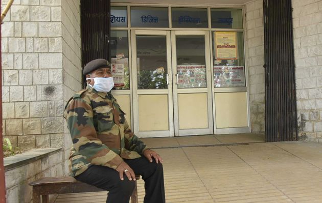 A guard is seen wearing a face mask as he sits outside the SMS hospital on January 27, 2020 in