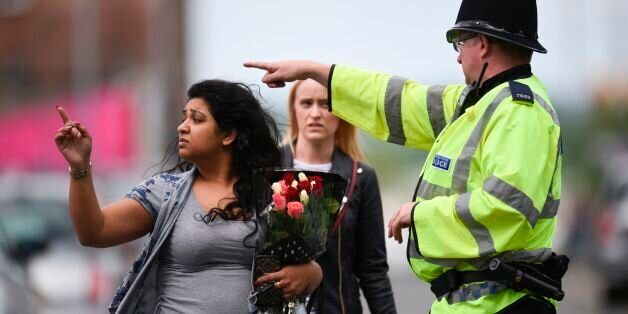 A police officer (R) directs a woman carrying a bunch of flowers near the Manchester Arena in Manchester,...