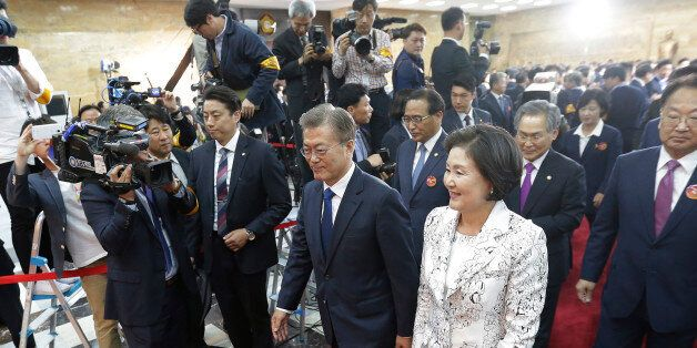 Newly elected South Korean President Moon Jae-in (L) and his wife Kim Jung-suk leave after his inauguration...