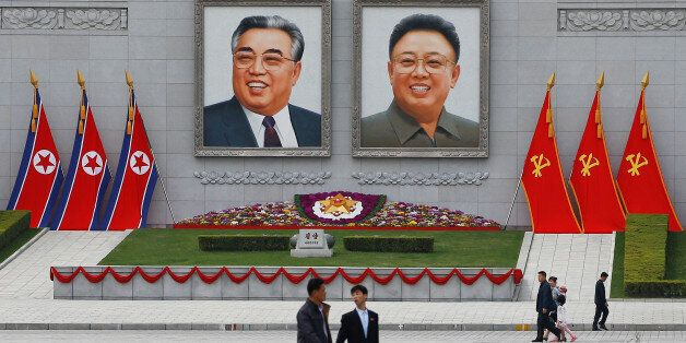 People walk in front of portraits of North Korea founder Kim Il Sung and late leader Kim Jong Il in central...