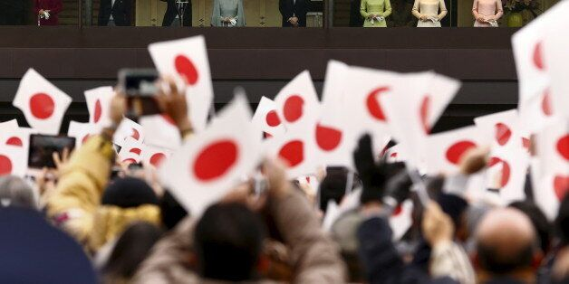 Japan's Emperor Akihito (3rd L), flanked by other members of the royal family, waves to well-wishers...
