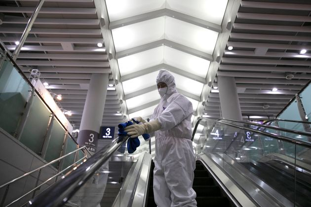 Workers from a cleaning and disinfection service spray disinfectant as part of efforts to prevent the...