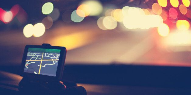 Night shot of GPS navigational system on dashboard of car. Traffic lights are visible through