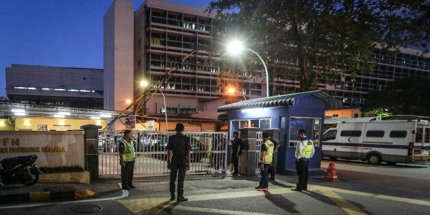 Police officers guard the entrance of the forensic department of Kuala Lumpur General Hospital, where...