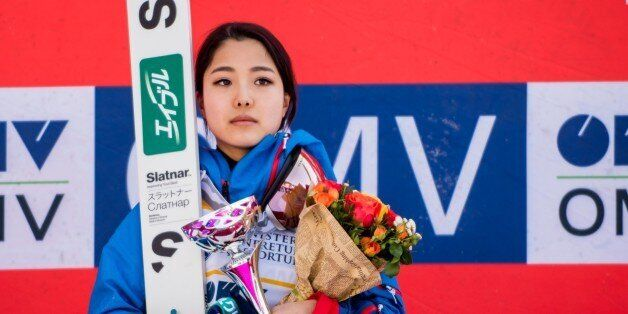 First placed Takanashi Sara of Japan poses on the podium after the Normal hill individual probe during...