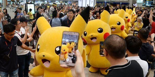 Fans gather to watch the Pokemon Go virtual reality game mascot Pikachu parade during a promotional event...