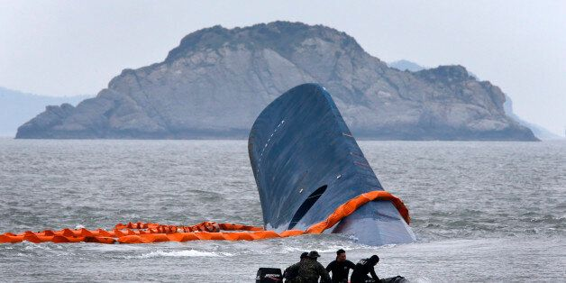 A vessel involved in salvage operations passes near the upturned South Korean
