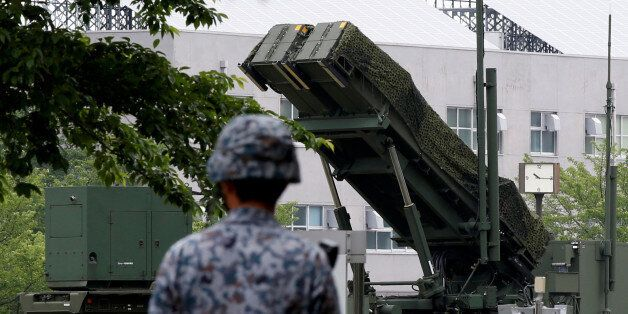 A Japan Self-Defence Forces soldier walks past Patriot Advanced Capability-3 (PAC-3) missile at the Defense...