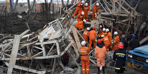 In this photo released by Xinhua News Agency, rescue workers look for survivors after a work platform...