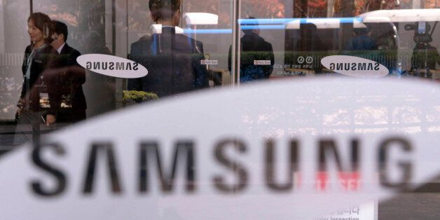 Employees walk past logos of Samsung Group at its headquarters in Seoul, South Korea, Wednesday, Nov....
