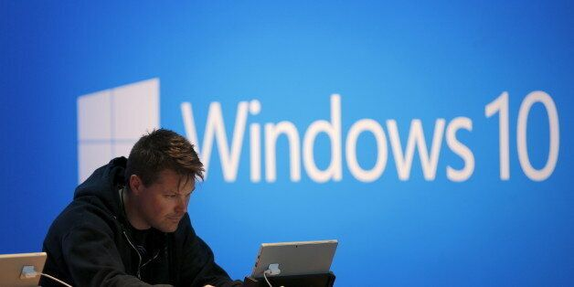 A man works on a laptop computer near a Windows 10 display at Microsoft Build in San Francisco, California...