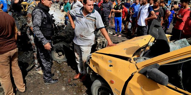 Security forces and citizens inspect the scene after a suicide car bombing hit a crowded outdoor market...