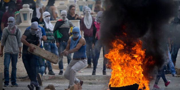 Palestinians improvise a barricade during clashes with Israeli troops near Ramallah, West Bank, Saturday,...