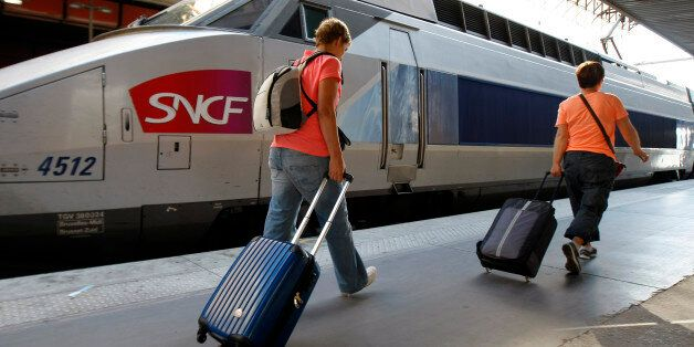People walk on a platform to take a TGV (High Speed Train) at the Gare St-Charles station in Marseille,...