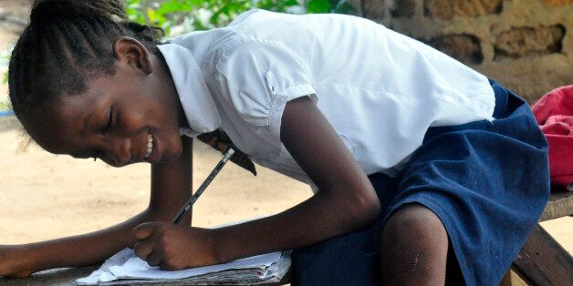 In this photo taken on Friday, May 8, 2015, Mercy Kennedy smiles as she does her home work after school...