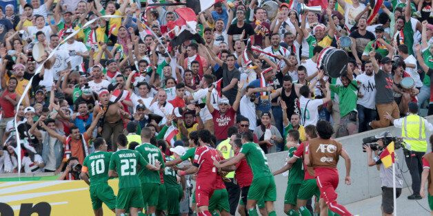 Iraqi players celebrate after scoring a goal during the AFC Asia Cup quarterfinal soccer match between...