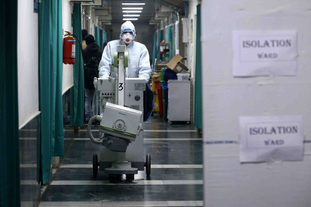 A medical staff member wearing protective clothing to help stop the spread of a deadly virus which began...