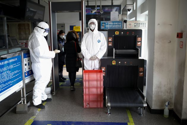 Staff members wearing protective suits and masks stand near the security check at a subway station, as...