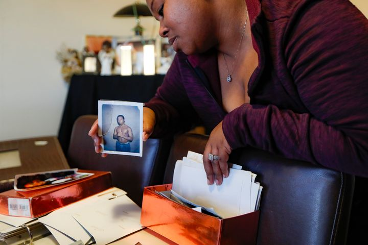 Ianna Burrell holds a photograph of her brother during his first year in prison as she pours over documents at her home, Frid