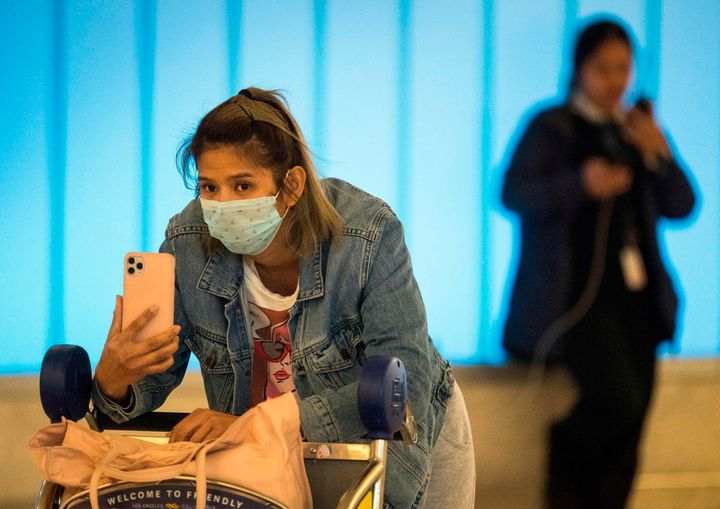 Passengers wear protective masks hoping to protect against the coronavirus as they arrive at Los Angeles International Airpor