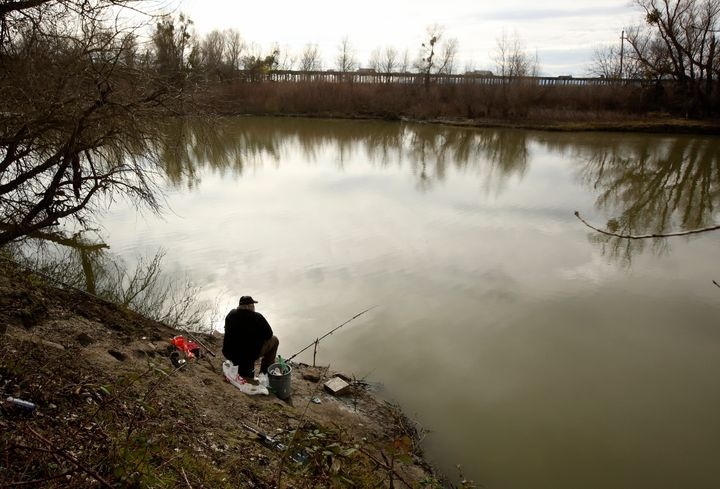 A fisherman sits along the slough where the body of an infant, Nikko Lee Perez, was discovered in Yolo County in 2007, near W