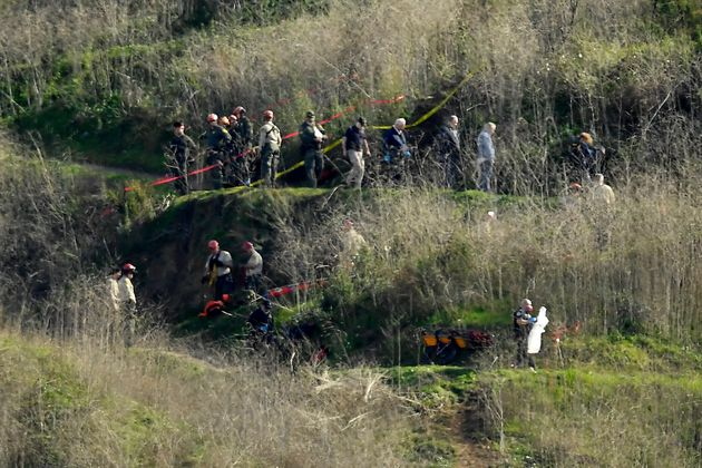 Investigators work the scene of a helicopter crash that killed former NBA basketball player Kobe Bryant,...