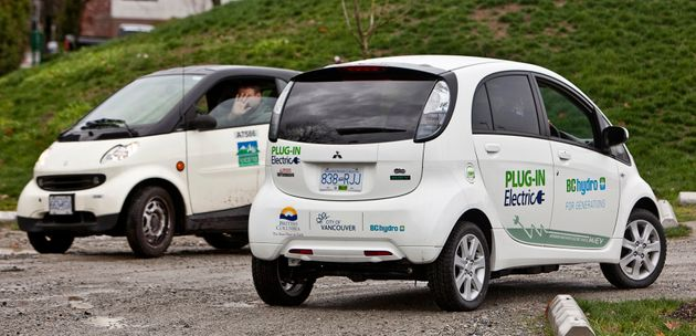 A city employee in a Smart Car waves to a colleague in a new Mitsubishi i-Miev electric car while leaving...