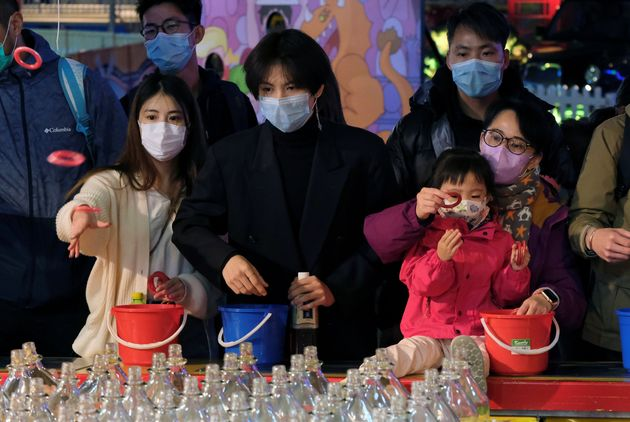 Visitors wear masks to prevent an outbreak of a coronavirus as they play at a carnival in Hong Kong,...