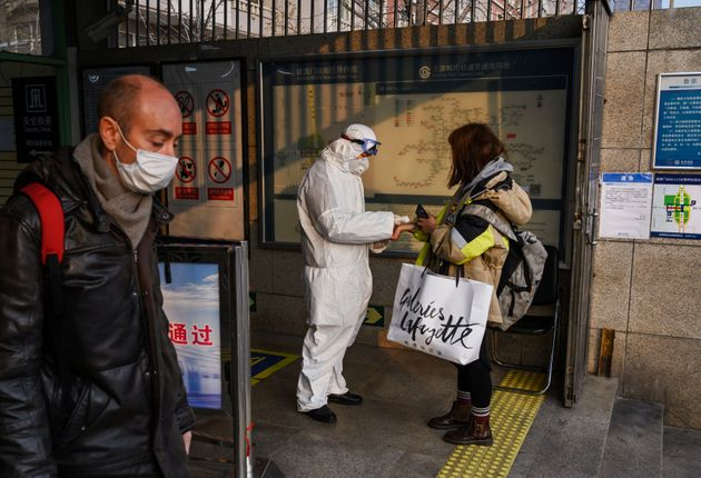 A Chinese worker is dressed in a protective suit as he takes the temperature of a woman at a subway station...