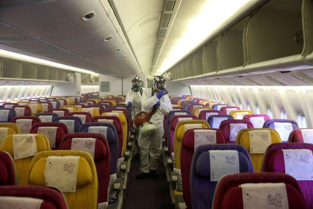 Miembros de la tripulación de Thai Airways desinfectan un