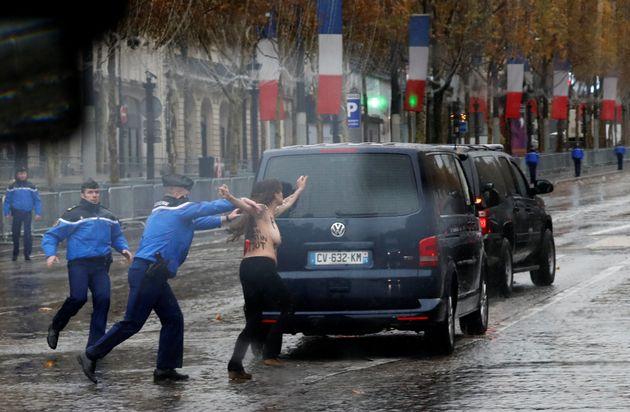 Une Femen perturbant le cortège de Donald Trump en route vers la cérémonie de commémoration...